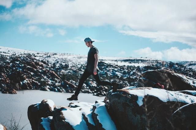 雪山を半そでで歩く男性