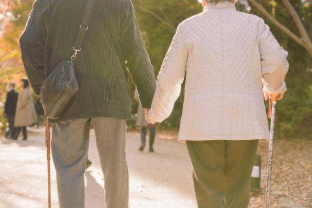 老夫婦が手をつないで歩いている