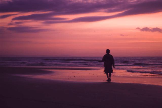 海辺を歩くおじさん