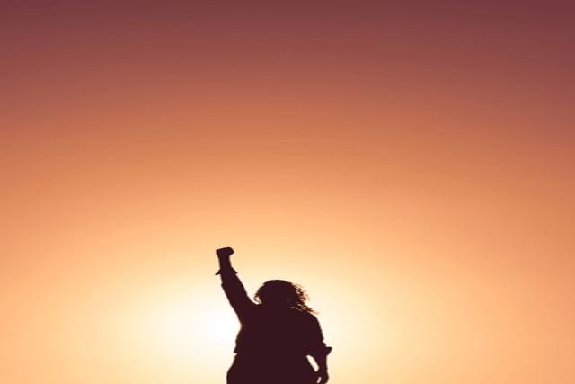 手を掲げている女性